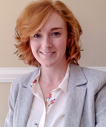 headshot of white woman with red hair wearing a cream blouse and light grey blazer