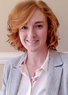 headshot of white woman with red hair wearing cream blouse and light gray blazer
